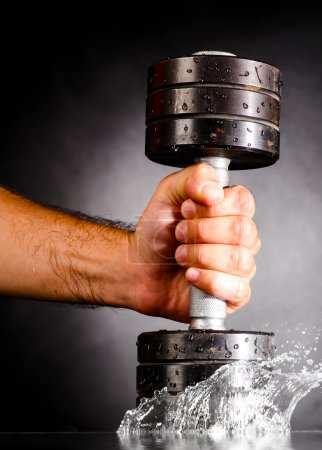 Photo for Male hand is splashing water with metal barbell - Royalty Free Image