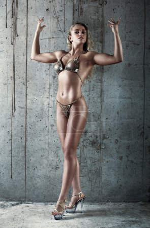Photo for Young sexy muscular woman on wall background. - Royalty Free Image