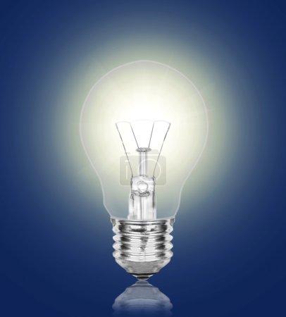 Photo pour Une lampe brûle brillamment sur un fond bleu foncé - image libre de droit