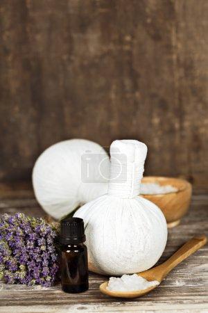 Photo pour Fleurs de lavande fraîche, sel, indispensable oii et herbal massage boules sur une surface en bois - image libre de droit