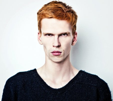 Young red haired man on light background.
