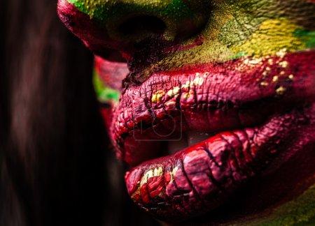 Photo pour Portrait en gros plan d'une femme artistique peinte en rouge et vert. Partie de la photo du visage . - image libre de droit