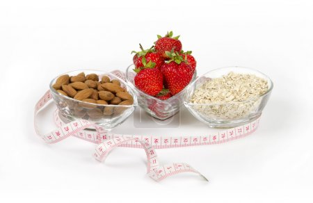 Photo for Healthy nutrition strawberry oatmeal and almond with a measuring tape - Royalty Free Image