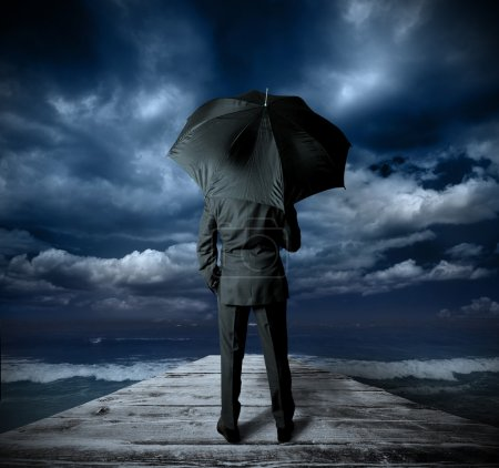 Photo for Businessman with umbrella against the storm - Royalty Free Image