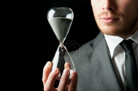 Photo for Businessman holding a hourglass with a girl inside - Royalty Free Image