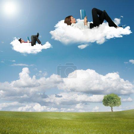 Foto de Chico y chica lectura libro sobre las nubes - Imagen libre de derechos