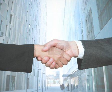 Photo pour Poignée de main d'affaires de femme d'affaires et d'homme d'affaires - image libre de droit