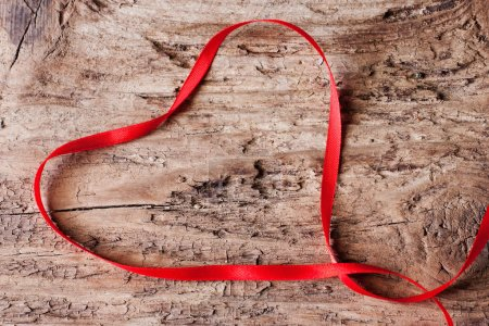 Tape in the form of heart on wooden background