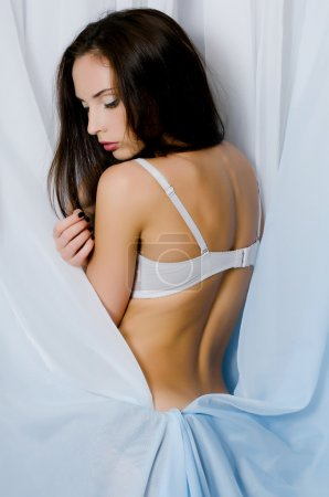 Photo for Beautiful girl in underwear a background of blue fabric - Royalty Free Image