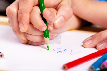 Photo for Child hand with pencil and woman hand helping to write letters - Royalty Free Image