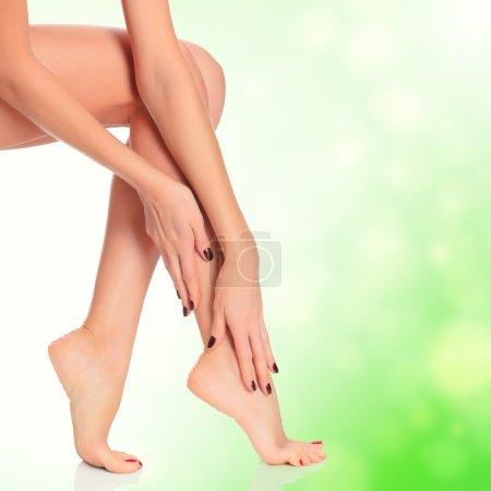 Female legs on green blurred background