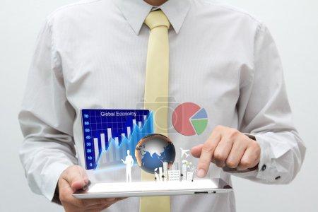 Photo pour Homme d'affaires tenant tablette PC avec graphique, graphique, tarte, globe et bâtiment volent hors de l'écran - image libre de droit