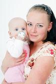 Dítě s dudlík v náručí matky
