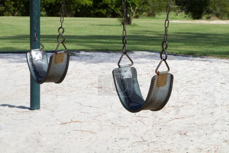 Foto de Columpios vacíos en un patio de vacante para ser utilizado como una imagen conceptual de abuso, los niños secuestrados o desaparecidos. - Imagen libre de derechos