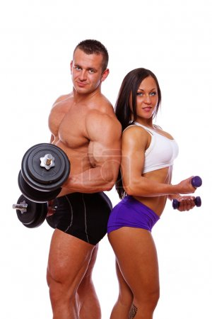 Portrait of couple posing in studio with dumbbells