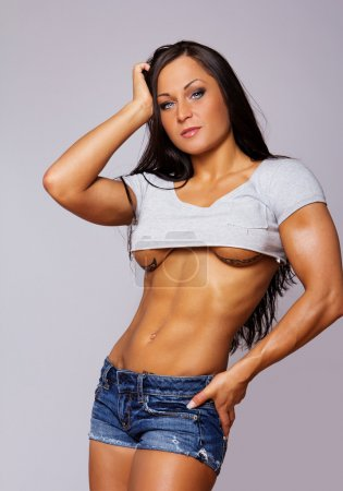 Portrait of muscle woman posing in gym on grey background
