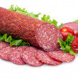 Tasty red sliced salami decorated with vegetables...