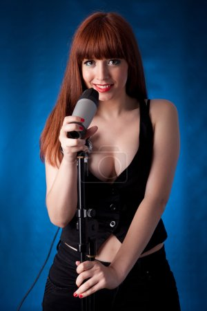 Photo pour Jeune et chaude chanteuse avec microphone - image libre de droit