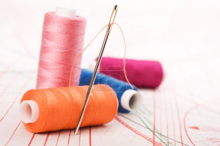 Photo for Spool of thread and needle. Sew accessories on blurred background. - Royalty Free Image