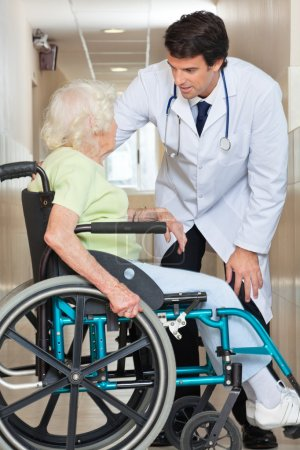 Doctor Communicating With Senior Woman Sitting In Wheelchair