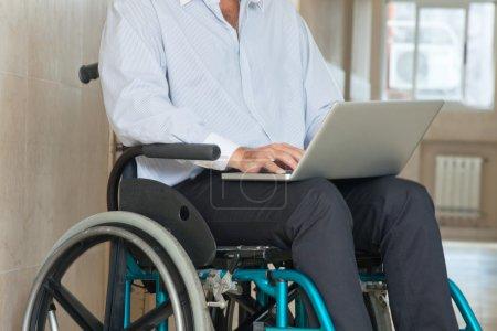 Man Sitting In Wheel Chair Using Laptop