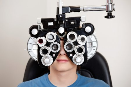 Photo for Boy sitting while undergoing an eye test with phoropter in the clinic - Royalty Free Image