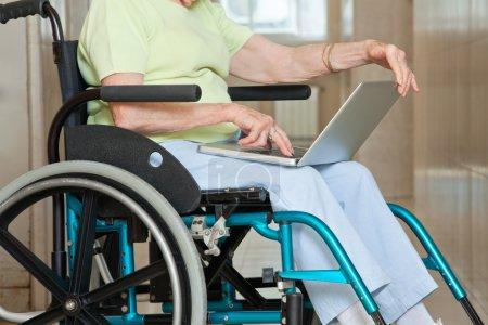 Senior Woman Sitting In Wheelchair Using Laptop