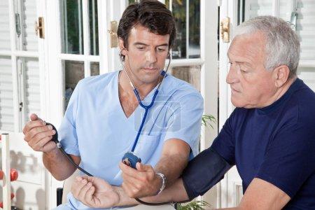 Photo pour Médecin prenant la pression artérielle d'un patient . - image libre de droit