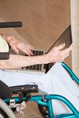 femme en fauteuil roulant à l'aide d'ordinateur portable