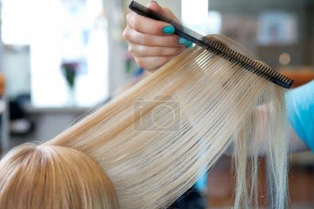 Photo pour Image recadrée de la main du coiffeur peigner les cheveux de la cliente au salon - image libre de droit