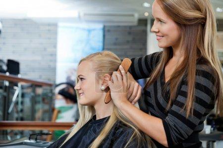 Hairdresser Combing Hair Of Female