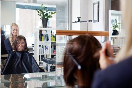 Photo pour Miroir reflet de jeune femme obtenant une coiffure par esthéticienne au salon - image libre de droit