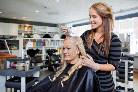 Photo pour Jeune femme ayant les cheveux teints par l'esthéticienne au salon - image libre de droit