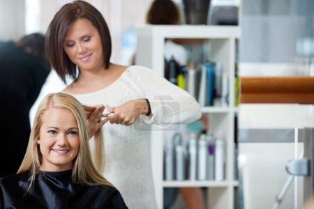 Photo pour Miroir reflet de coiffeur donnant une coupe de cheveux à la femme au salon - image libre de droit