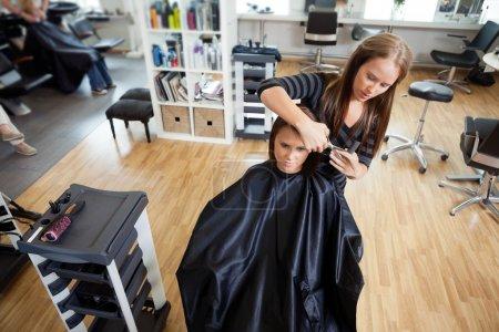 Photo pour Vue grand angle du client féminin se faire couper les cheveux par l'esthéticienne au salon - image libre de droit
