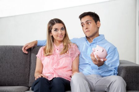 Man Holding Piggybank While Sitting With Woman