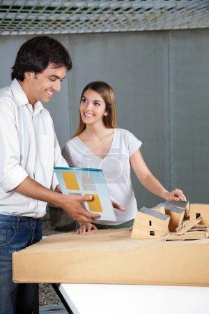 Photo pour Jeune architecte masculin regardant la maison modèle tandis que collègue féminin lui souriant - image libre de droit