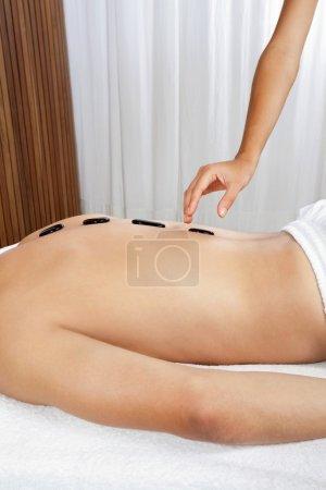 Photo pour Homme au spa recevant le massage aux pierres chaudes de thérapeute - image libre de droit