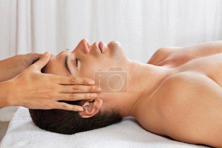 Photo pour Vue latérale du jeune homme recevant un massage de la tête au spa de santé - image libre de droit