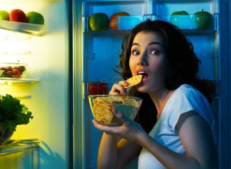 Photo for A hungry girl opens the fridge - Royalty Free Image