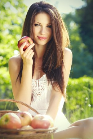 Photo pour Femme d'Apple. très beau modèle ethnique mange pomme rouge dans le parc. - image libre de droit