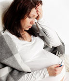 Pregnant woman with a thermometer