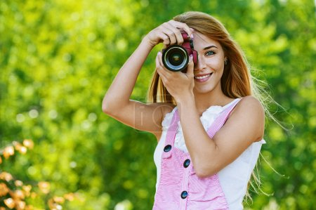 Smiling young woman with camera
