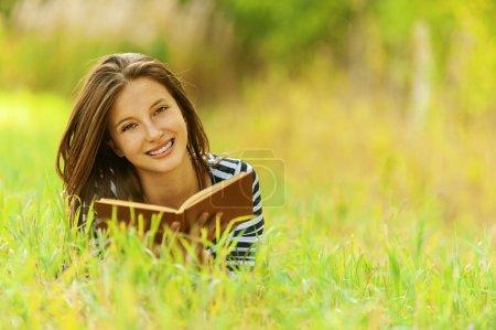 Photo pour Belle jeune femme souriante allongée sur l'herbe livre de lecture, contre le vert du parc d'été . - image libre de droit