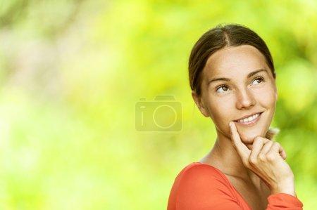Photo pour Portrait de songeuse belle jeune brune en blouse rouge de près, contre le vert du parc de l'été. - image libre de droit