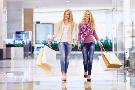 Photo for Beautiful girls with shopping bags walking in the store - Royalty Free Image