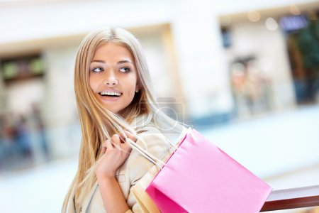 Photo for Smiling girl with shopping bags in shop - Royalty Free Image