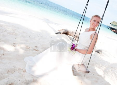 Beautiful bride swinging on tropical sea side background
