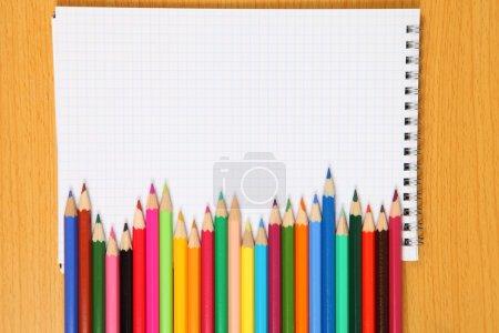 Photo pour Crayons de couleur et carnet de notes sur une table en bois. Gros plan . - image libre de droit