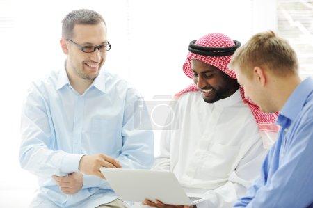 Photo pour Multicultural ethnie différente collaborant sur ordinateur portable - image libre de droit